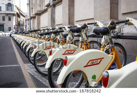 MILAN, ITALY Â?Â? JULY 9, 2013: A row of public city bicycles in the center of Milan. One unrecognizable person visible in far background. Public bicycle system in Milan is operated by the bikeMi company - stock photo