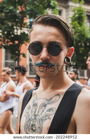 MILAN, ITALY - JUNE 28: People at gay pride parade in Milan JUNE 28, 2014. Thousands of people march in the city streets for the annual gay pride parade, claiming equality and legal rights.  - stock photo