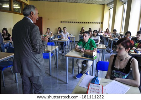 MILAN, ITALY-JUNE 20, 2012: Teacher classroom with college students seated on school desk in the exam room, for the secondary school's final exams, at the Artemisia Gentileschi School in Milan. - stock photo