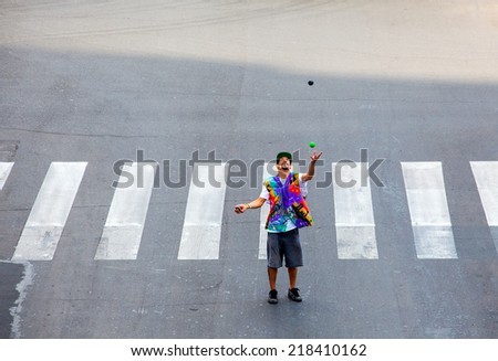 MILAN, ITALY - MAY, 27: Juggler in the crossing road on May 27, 2014 - stock photo