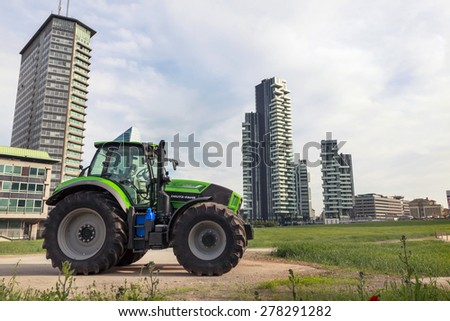 MILAN, ITALY, May 12, 2015: The areas around the new skyscrapers built in the district of Porta Garibaldi, have green spaces and farmland. - stock photo