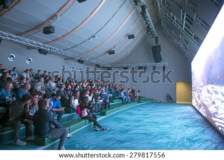 MILAN, ITALY-MAY 04, 2015: visitors attending a video presentation on a movie theatre inside the China pavillion at the EXPO 2015, in Milan. - stock photo