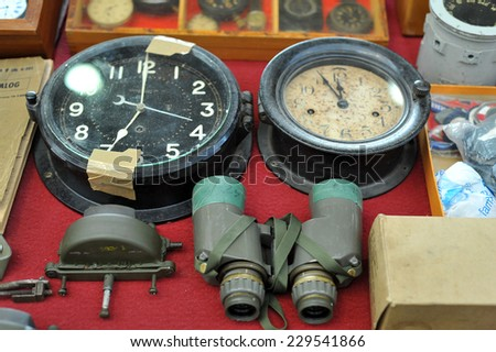 MILAN, ITALY - NOV 1: Old clocks and binoculars, Exhibitor sitting in his stand at Militalia, exhibition dedicated to militaria collectors and military associations on November 1, 2014 in Milan. - stock photo