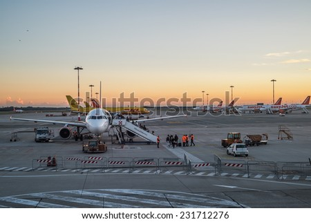 MILAN, ITALY - NOV 18: People board a commercial airplane at Milan Malpensa airport at sunset in Milan on November 18, 2014 - stock photo