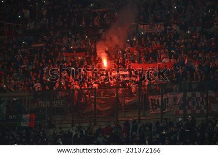 MILAN, ITALY-NOVEMBER 16, 2014: croatian fans light a smoke bomb during the international soccer match Italy vs Croatia, in Milan. - stock photo
