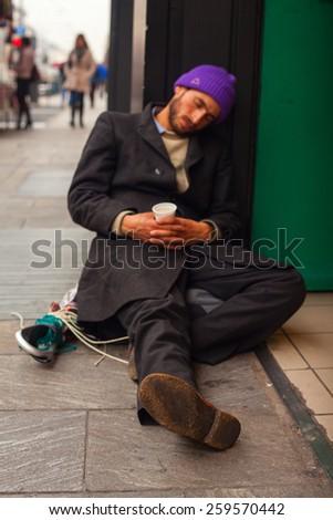 MILAN, ITALY - NOVEMBER, 24: Homeless sleeping in the floor of the street on November 24, 2014 - stock photo