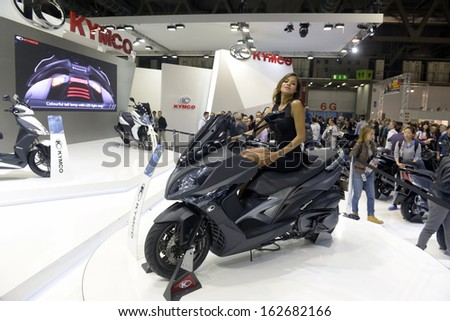 MILAN, ITALY - NOVEMBER 8: People visit Kymco motorcycles and scooters exhibition area at EICMA, 71st International Motorcycle Exhibition on November 8, 2013 in Milan, Italy.