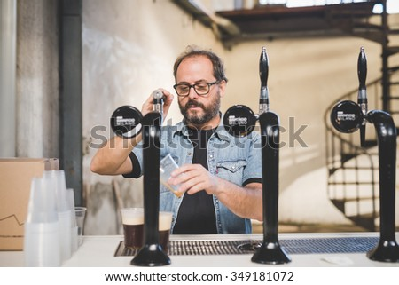 MILAN, ITALY - NOVEMBER 7: People visiting Eat Market, a street food parade with international dishes  in Milan on November, 7 2015. Salesman of Birrificio Milan stapling some beers for customer