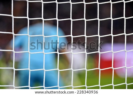 MILAN, ITALY-NOVEMBER 02, 2014: soccer goal net with blurry goalkeeper during the italian serie A soccer match AC Milan vs Palermo, at the san siro stadium, in Milan. - stock photo