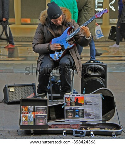 MILAN, ITALY - NOVEMBER 27, 2015: street musician is playing guitar in outdoor in Milan, Italy - stock photo