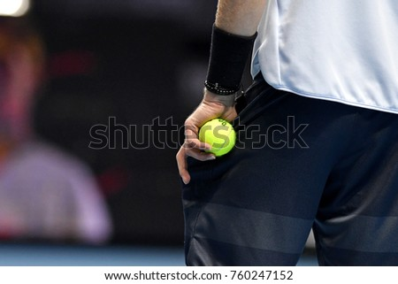 MILAN, ITALY-NOVEMBER 11, 2017: tennis player close up hand holding yellow tennis ball while service, during the Next Gen ATP professional tournament, in Milan.
