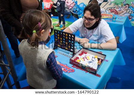 MILAN, ITALY - NOVEMBER 22: Young girl plays Connect Four at G! come giocare, trade fair dedicated to games, toys and children on NOVEMBER 22, 2013 in Milan. - stock photo