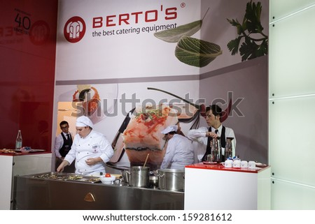 MILAN, ITALY - OCTOBER 18: A young chef prepares food at Host 2013, international exhibition of the hospitality industry on OCTOBER 18, 2013 in Milan. - stock photo