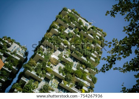 MILAN, ITALY - OCTOBER 9, 2017: Bosco Verticale, vertical forest apartment buildings and poplar branches in the business district of Porta Garibaldi, warm toned