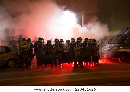 MILAN, ITALY - OCTOBER 11: Demonstrators launch smoke canisters to police in front of the Turkish consulate while asking help for Kurdish people in Syria on OCTOBER 11, 2014 in Milan. - stock photo