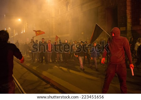 MILAN, ITALY - OCTOBER 11: Demonstrators launch smoke canisters to police in front of the Turkish consulate while asking help for Kurdish people in Syria on OCTOBER 11, 2014 in Milan.