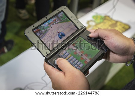MILAN, ITALY - OCTOBER 24: Detail of Nintendo handheld console at Games Week 2014, event dedicated to video games and electronic entertainment on OCTOBER 24, 2014 in Milan. - stock photo