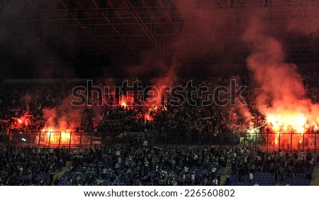 MILAN, ITALY-OCTOBER 23, 2014: french soccer fans lighting smoke flares at san siro stadium, during the Europa League match FC Internazionale vs ST Etienne, in Milan.