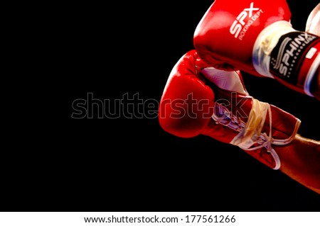 MILAN, ITALY-OCTOBER 17, 2006: Isolated red boxing gloves with black background during a professional boxing match. - stock photo