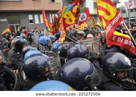 MILAN, ITALY-OCTOBER 08, 2014: policemen with helmets, shield and truncheon stop a rally protest against italian government's work reform, in Milan. - stock photo
