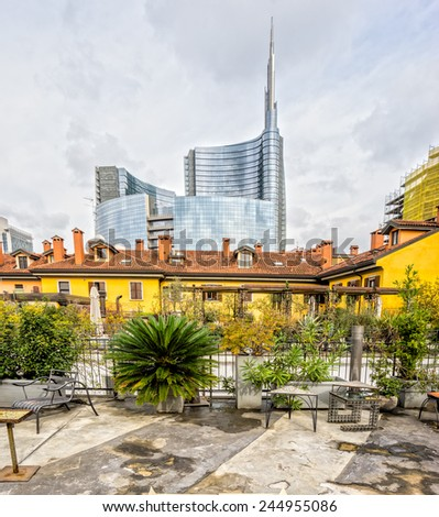 MILAN, ITALY - OCTOBER 15,2014:  Traditional milanese historic house in the foreground with the new modern glass building of Unicredit in the background, Porta Nuova Area. - stock photo