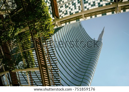 MILAN, ITALY - OCTOBER 9, 2017: View of the Unicredit skyscraper tower complex with a green decorative plants on the roof, Piazza Gae Aulenti, warm toned filter