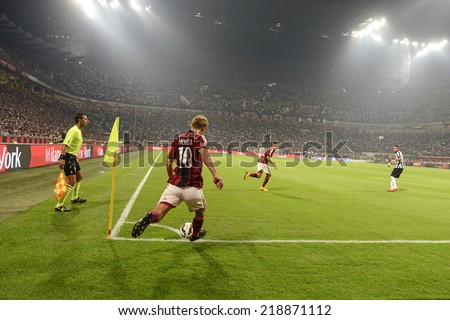 MILAN, ITALY-SEPTEMBER 20, 2014: japanese AC MIlan soccer player Keisuke Honda kicks a corner at the San Siro stadium, during the professional serie A soccer match AC Milan vs Juventus, in Milan. - stock photo