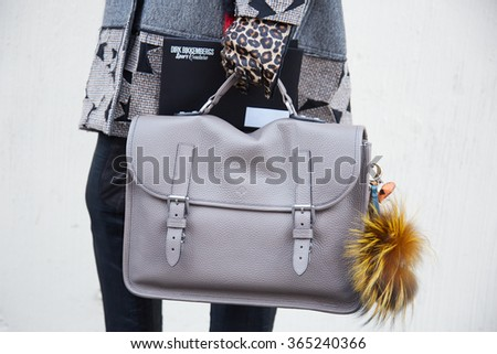 MILAN - JANUARY 19: Man poses for photographers with Mulberry leather bag and Fendi accessory before Bikkembergs fashion show on January 19, 2015 in Milan, Italy. Man fashion fall winter 2016 / 2017 - stock photo