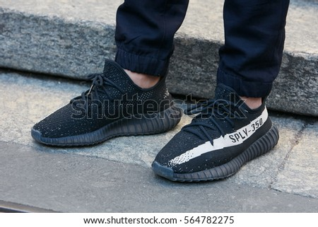MILAN - JANUARY 15: Man with Adidas Yeezy Boost 350 black shoes before  Salvatore Ferragamo