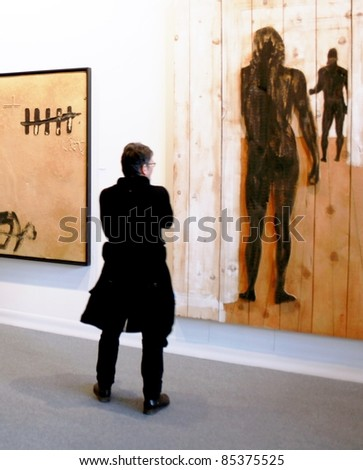 MILAN - MARCH 27: Visitor looks at work of arts galleries during MiArt ArtNow, international exhibition of modern and contemporary art March 27, 2010 in Milan, Italy.