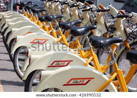MILAN - MAY 8: Bike sharing service racks in Milan on May 8, 2016 in Milan, Italy. The yellow Bikemi bicycles are availabe for rental with the public transport ticket. - stock photo