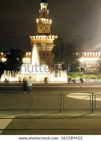 MILAN-SEPT. 24: Monumental tower in front of Sforza Castle in Milan, Italy is lighted at night as fountains flow with water on September 24, 2015. - stock photo