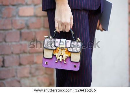 MILAN - SEPTEMBER 24: Woman poses for photographers before Fendi show with bag with gold griffin during Milan Fashion Week Day 2, Spring / Summer 2016 street style on September 24, 2015 in Milan. - stock photo