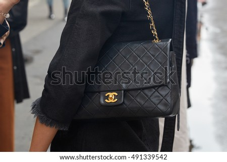 MILAN - SEPTEMBER 21: Woman with black Chanel leather bag before Wunderkind fashion show, Milan Fashion Week street style on September 21, 2016 in Milan.