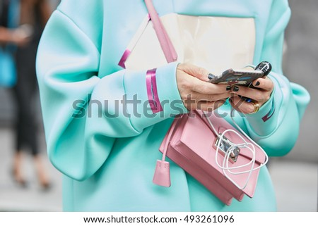 MILAN - SEPTEMBER 23: Woman with pink bag and pale blue clothes before Giorgio Armani fashion show, Milan Fashion Week street style on September 23, 2016 in Milan.