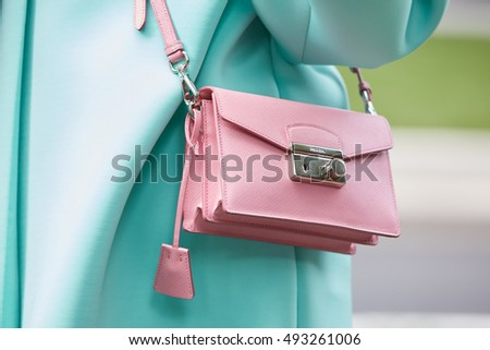 MILAN - SEPTEMBER 23: Woman with pink leather Prada bag and pale blue coat before Giorgio Armani fashion show, Milan Fashion Week street style on September 23, 2016 in Milan.