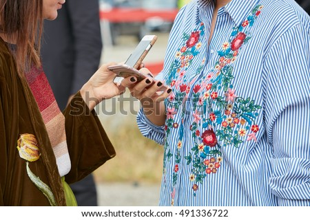 MILAN - SEPTEMBER 21: Women checking smartphone with floral embroidery shirts before Gucci fashion show, Milan Fashion Week street style on September 21, 2016 in Milan.