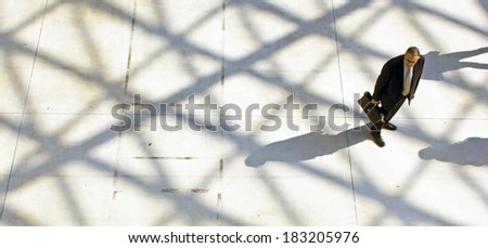 MILANO, ITALY - APRIL 10, 2013: Man waiting at the entrance of Salone del Mobile, international furnishing accessories exhibition at Rho Fiera Center in Milano, Italy.  - stock photo