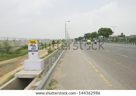 Milestone at the roadside, National Highway 8, New Delhi, India - stock photo