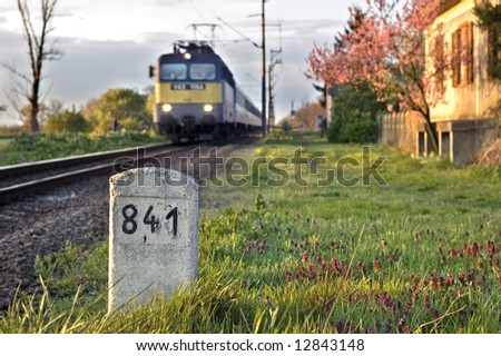 Milestone with old house and train - stock photo