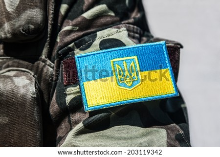 military badge of ukrainian army with trident and yellow-blue flag - stock photo