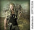Military Camouflaged man in forest with automatic and hand gun - stock