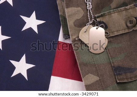 Military Dog Tags on American Flag and fatigues - stock photo