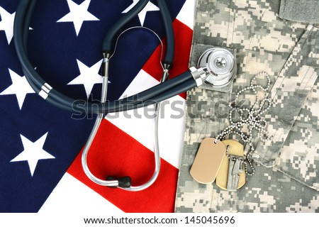 Military fatigues and dog tags on an American Flag with a stethoscope to illustrate health care in the armed services. Horizontal format, fills the frame. - stock photo