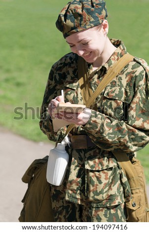 Military female writing in notebook outdoor - stock photo