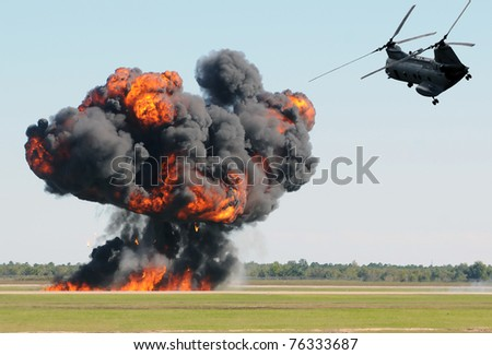 Military helicopter flying over ground explosion - stock photo