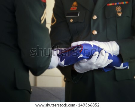Military honor guard carefully folds the United States flag for presentation to family members at a veteran's funeral. Selective focus on flag and gloved hands.  - stock photo