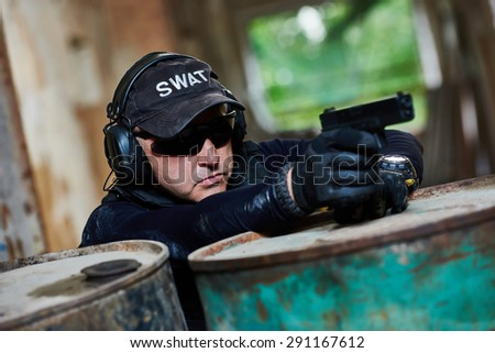 Military industry. Special forces or anti-terrorist police soldier,  private military contractor armed with pistol ready to attack during clean-up operation, mission - stock photo