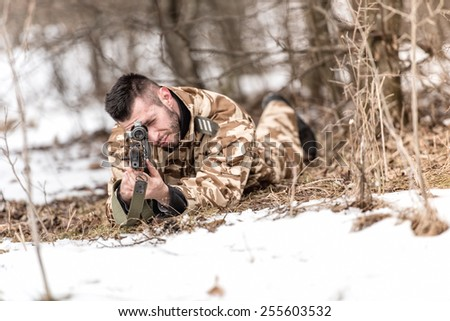 military man in combat uniform holding a gun and shooting outdoors. Hunting or military concept - stock photo