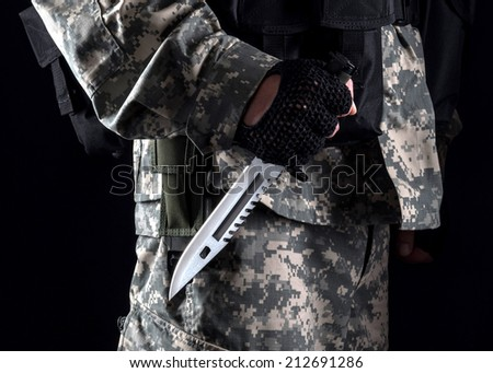 Military Man With A Knife In Hand Close Up On The Black Background